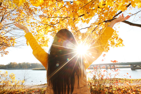 Happy woman with raised hands in autumn park Stockfoto