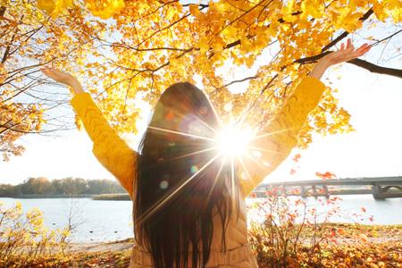 Happy woman with raised hands in autumn park Standard-Bild