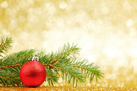 shiny background: Christmas card with fir branch and decorations on golden gitter background