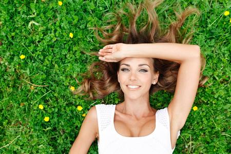 NATURE: joven y bella mujer de vestido blanco tumbado en la hierba