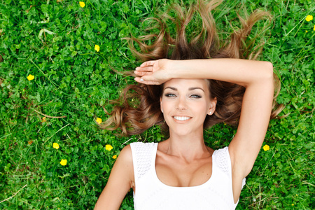 beautiful young woman in white dress lying on grass Stockfoto