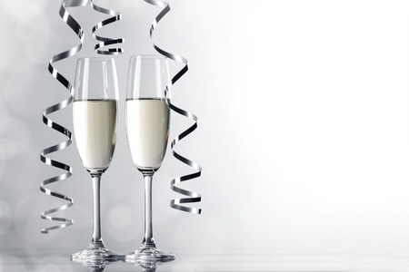 festive occasions: Two glasses of champagne and ribbons on light bokeh background Stock Photo