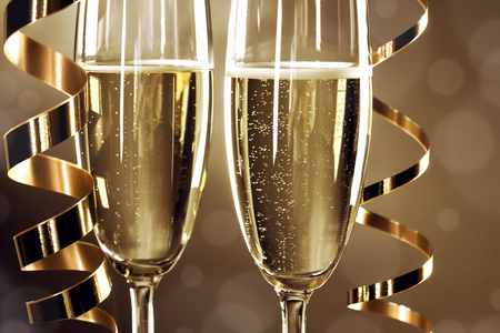 tomando alcohol: Dos copas de champ�n y cintas rizadas sobre fondo oscuro