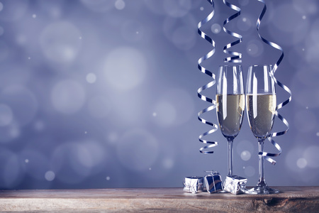 champagne glasses: Two champagne glasses and curly ribbons on dark background