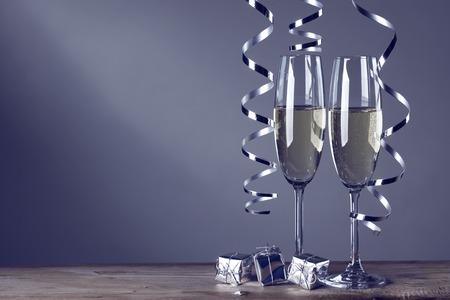 dark blue: Two champagne glasses and curly ribbons on dark background