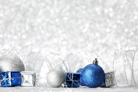 and of blue: Decorative Christmas balls and gifts on silver bokeh background Stock Photo