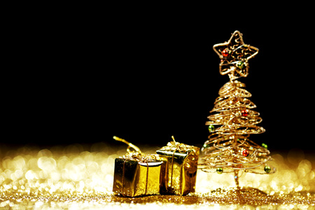 shiny black: Beautiful golden decorative christmas tree and gifts on golden glitter background