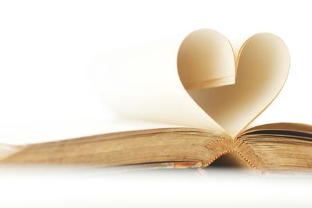 forme: Pages de livre ouvert laminé en forme de coeur isolé sur blanc