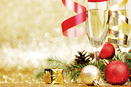 champagne glasses: Champagne, fir tree, christmas decor and gifts on golden background