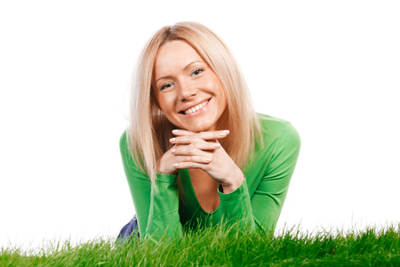 Young happy woman lying on spring grass, isolated on white background photo