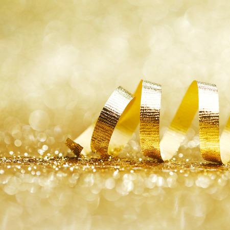 축하: 반짝이 배경 근접에 황금 곱슬 리본 장식