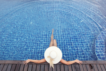 relaxation: Woman in big hat relaxing in swimming pool