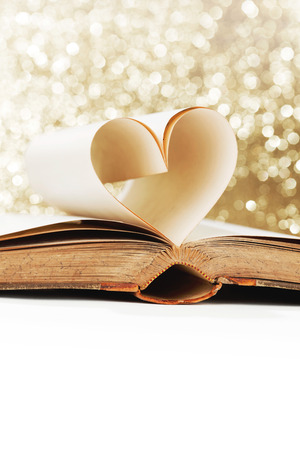 book pages: Heart shaped book pages on glitter background Stock Photo