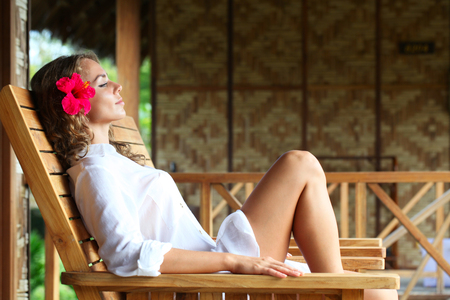 chaise lounge: Young beautiful woman relaxing on chaise lounge
