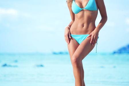 Krásná slunce opálená žena v plavkách na mořské pozadí