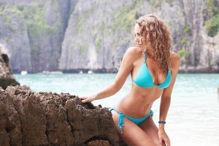 sea beach: Beautiful woman in bikini posing in thai beach with rocks