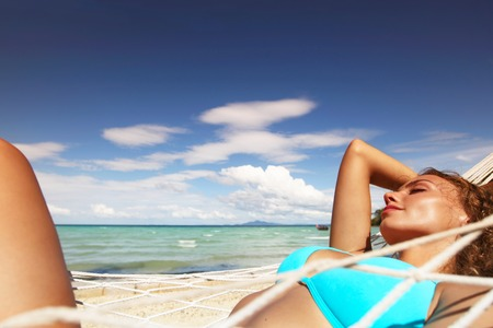 hummock: Young beautiful woman resting in hummock on tropical beach Stock Photo