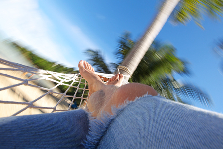 people relax: Feet of man relaxing in a hammock on beach close-up