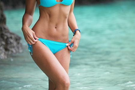 cuerpo femenino: Hermosa mujer en bikini posando en la playa tailandesa con las rocas