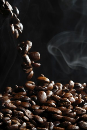 grano de cafe: Falling roasted coffee beans with steam on black Foto de archivo