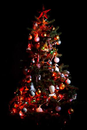 shiny black: Christmas tree with shiny ornaments isolated on black
