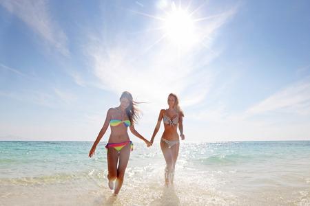manos sosteniendo: Dos mujeres sonrientes en bikini caminando desde el mar a la playa