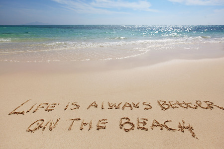better: Life is always better on the beach, conceptual handwriting on sand Stock Photo
