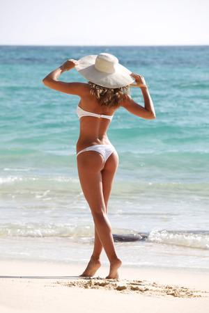 sunhat: Woman in sunhat and bikini standing on ocean beach on hot summer day