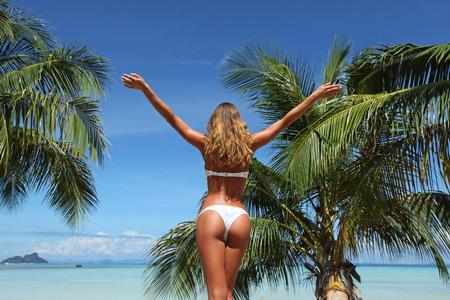 Schöne junge Frau, die auf tropischen Strand mit erhobenen Händen