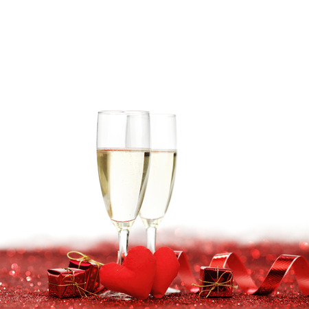 alcohol drinks: Glasses with Champagne and handmade hearts on red glitters isolated on white background Stock Photo