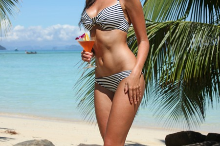 Beautiful woman with cocktail posing on tropical beach