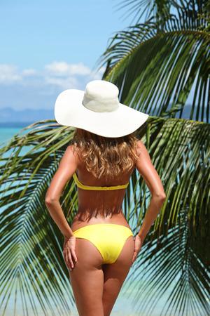 sunhat: Woman in sunhat standing on tropical beach