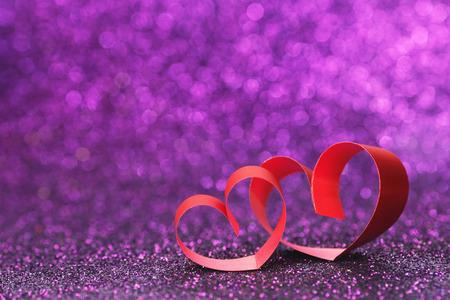 purple ribbon: Decorative hearts of red ribbon on shiny glitter background