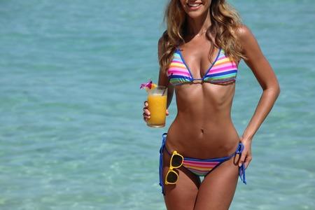 Schöne Frau im Bikini mit Cocktail am Strand