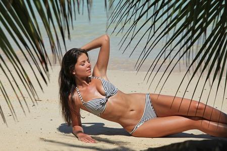 Woman in bikini laying on tropical beach Stock Photo