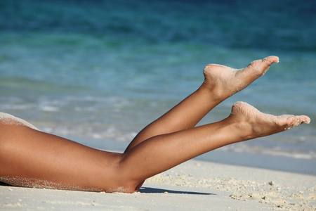 women legs: Beautiful tan female legs on sea beach