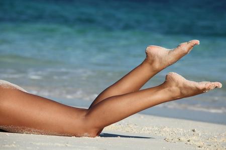 piernas sexys: Hermosas piernas femeninas bronceado en la playa del mar