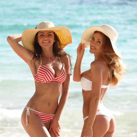 Happy smiling female friends in bikini and sunhats on vacation