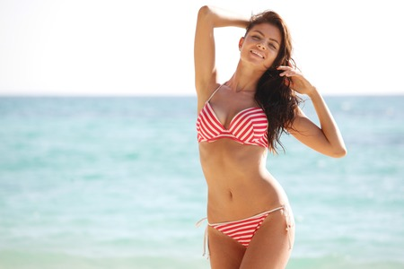 brunette: mujer feliz en bikini posando en la playa en Tailandia