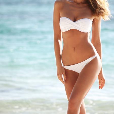 Woman with perfect body in bikini over blue sea background 스톡 콘텐츠