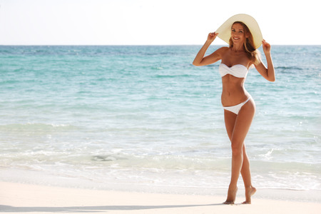 Frau im Bikini und Sonnenhut am Strand