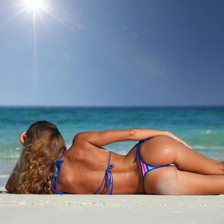 lying on back: Rear view of sexy woman in bikni lying on topical beach