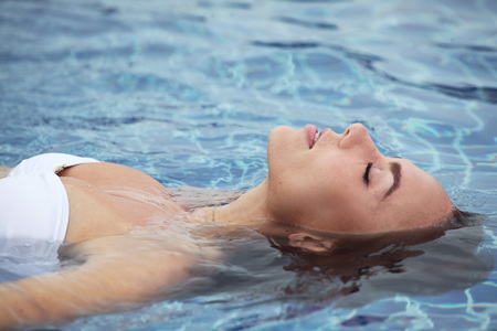 woman floating: Close up view of an attractive young woman floating in swimming pool Stock Photo