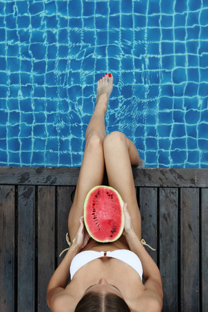 tanned body: Beautiful woman with fit, tanned body in bikini with watermelon tanning poolside