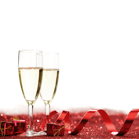 copa de vino: Glasses with Champagne and gifts on red glitters isolated on white background