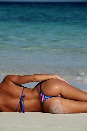petite fille maillot de bain: Vue arrière de la femme sexy en bikni couchée sur la plage locale