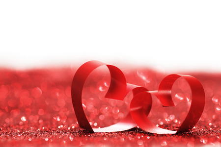 Red ribbon hearts on glitters isolated on white, Valentines day concept