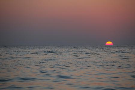 pink skies: Beautifulk round sun at sunset time over sea Stock Photo