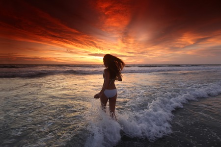 seminyak: Happy woman running on the beach at sunset, Bali, Seminyak, Double six beach Stock Photo