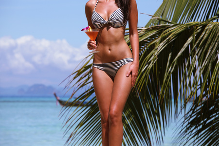sexy female body: Beautiful woman with cocktail posing on tropical beach